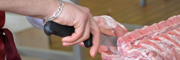 apprenti boucher qui découpe sa viande