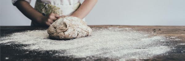 boulanger qui roule le pain dans la farine