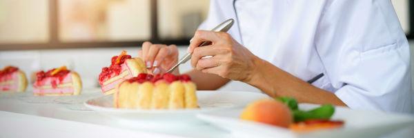 chef qui dresse un dessert dans une assiette