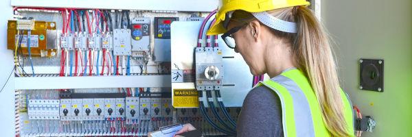 femme électricienne devant un tableau électrique