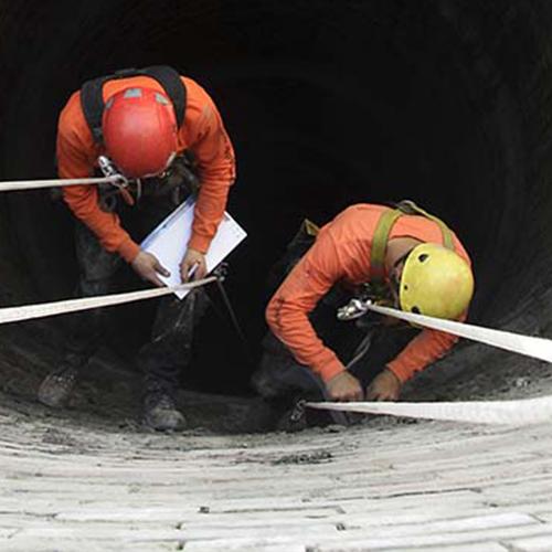 deux artisans descendent en rappel dans un puit