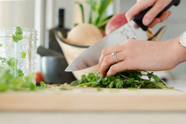 personne qui découpe des légumes sur une planche à découper