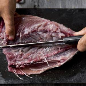 poissonnier qui découpe le poisson