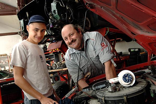 un mécanicien pose avec son apprenti