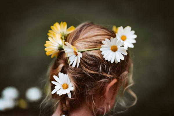 une fillette de dos avec des pâquerettes dans les cheveux