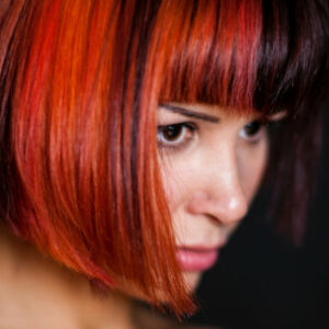 femme avec une coupe de cheveux courts et colorés en bordeaux