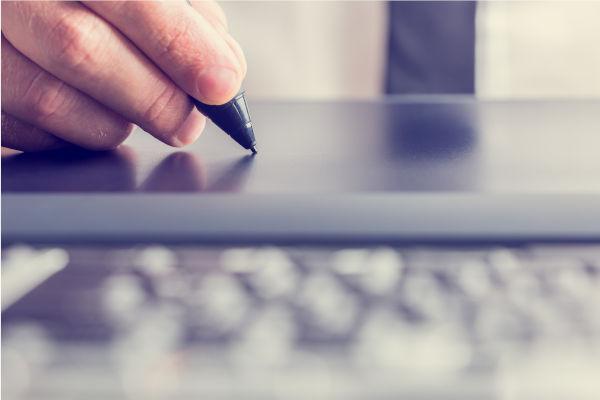 personne qui écrit avec un stylet sur une tablette