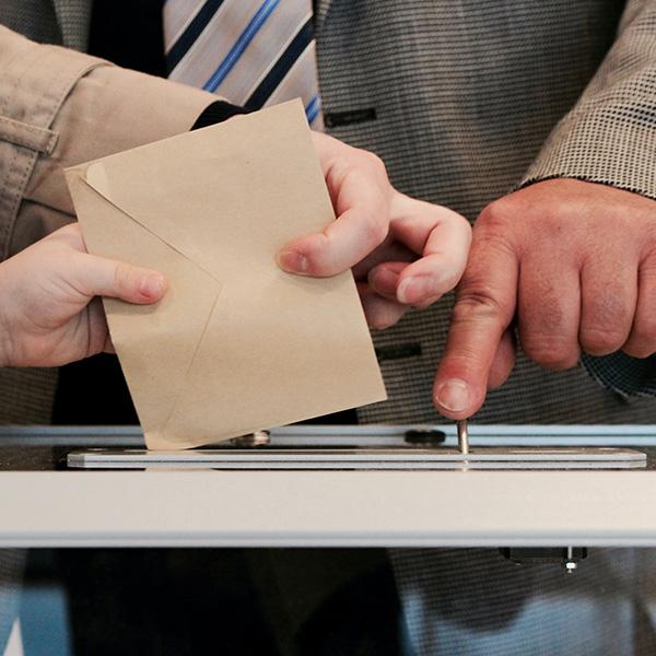 main qui met une enveloppe dans une urne pour voter