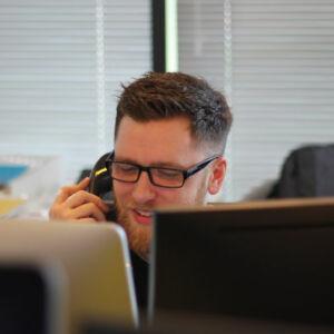 homme derrière un bureau qui parle au téléphone
