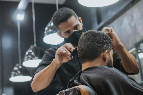 un coiffeur avec un masque qui coiffe un homme