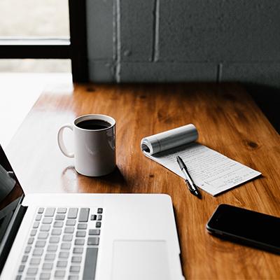 bureau avec un ordinateur, un bloc note et une tasse de café