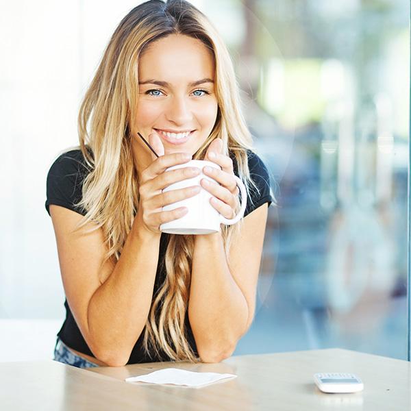 fille blonde avec son café sur un bureau