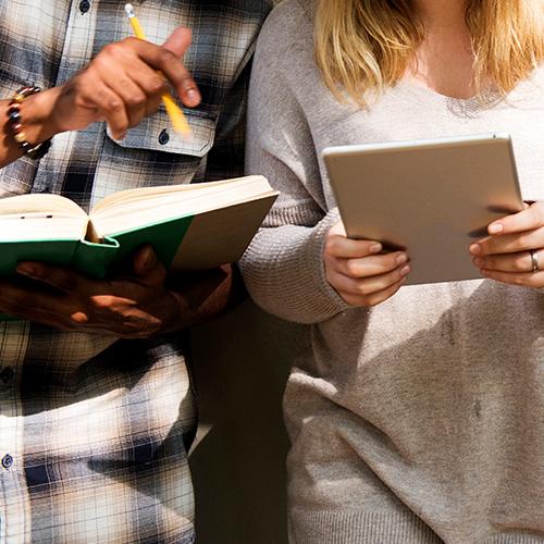 deux personnes avec un livre et une tablette