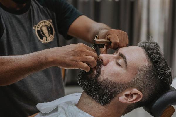 un homme se fait raser chez le barbier