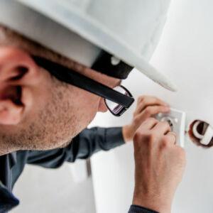 électricien qui répare une prise