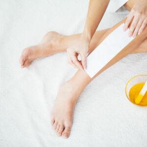 une femme s'épile la jambe à la cire
