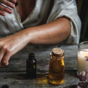 une femme qui se passe des huiles essentielles sur le bras