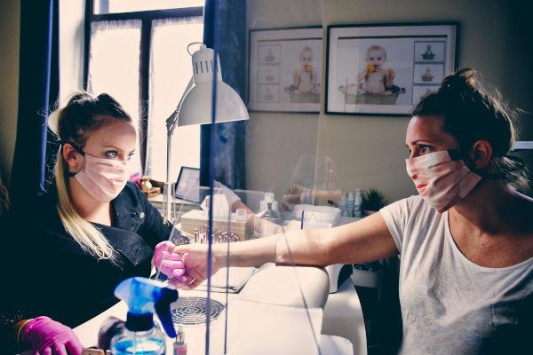 femme avec une cliente portant des gants dans un salon de beauté