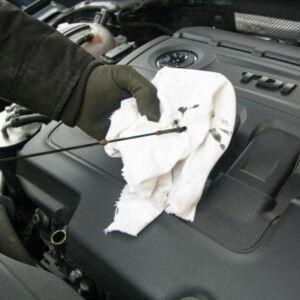 mécanicien qui regarde le niveau d'huile sur une voiture