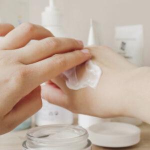 femme qui se passe de la crème sur les mains
