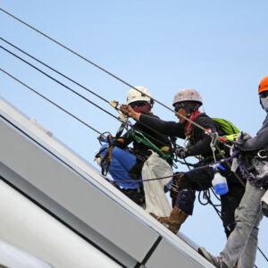 des hommes équipés de harnais travaillant en hauteur