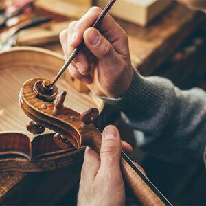 luthier en train de peindre un instrument