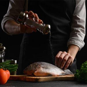 personne cuisinant un poisson