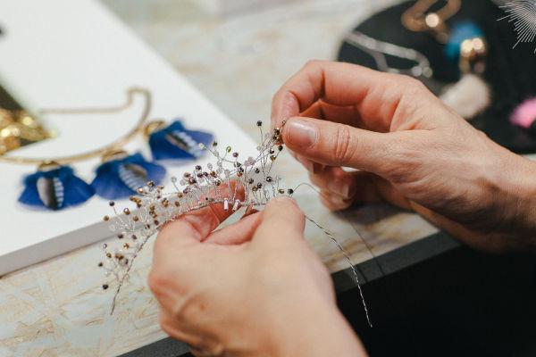 artisane qui fabrique une couronne en bijoux