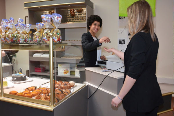 une apprentie vendeuse rend la monnaie à une cliente