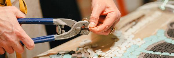 femme qui coupe des morceaux de mosaïque